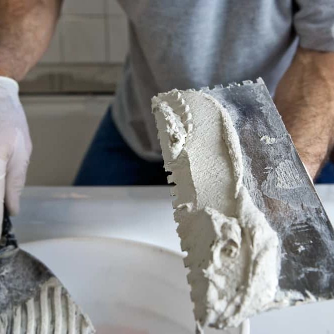 Man Working with Trowel and Mortar Tiling a Bathroom Wall. Closeup with selective focus on trowel and mortar